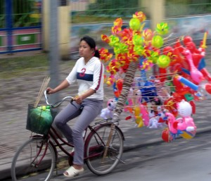 Vietnamese cyclist with balloons - smaller
